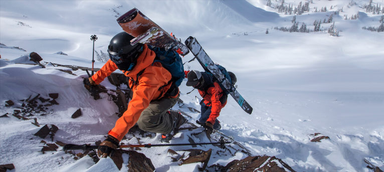 Picture of two guys climbing a snowy rock wall with their skis attached to their packs